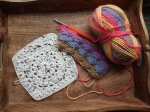 Circle of friends on the left and the beginning of a shell stitch square on the right... both with yarn from Katy the Night Owl